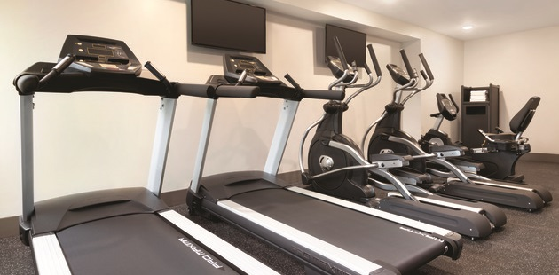 Fitness room with cardio machines and flat-screen TVs