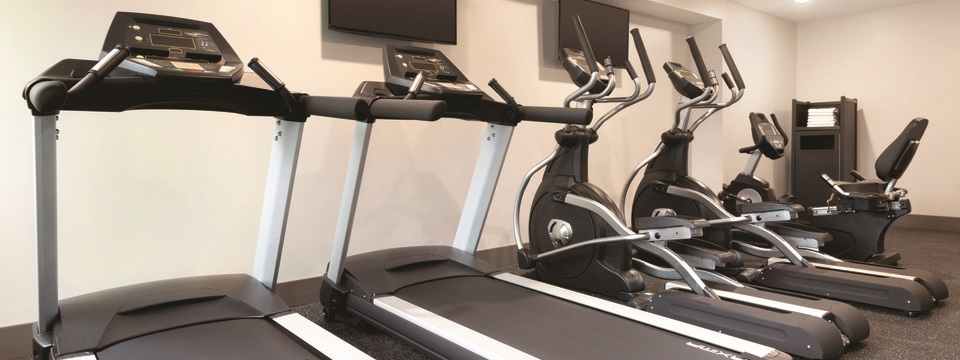 Fitness center with cardio machines and flat-screen TVs