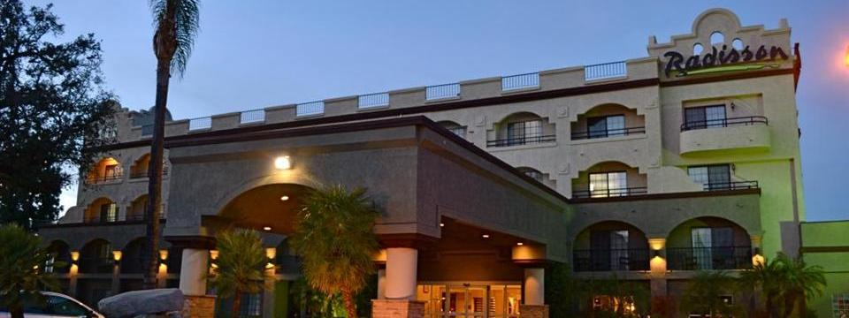 Hotel exterior featuring a carport and balconies