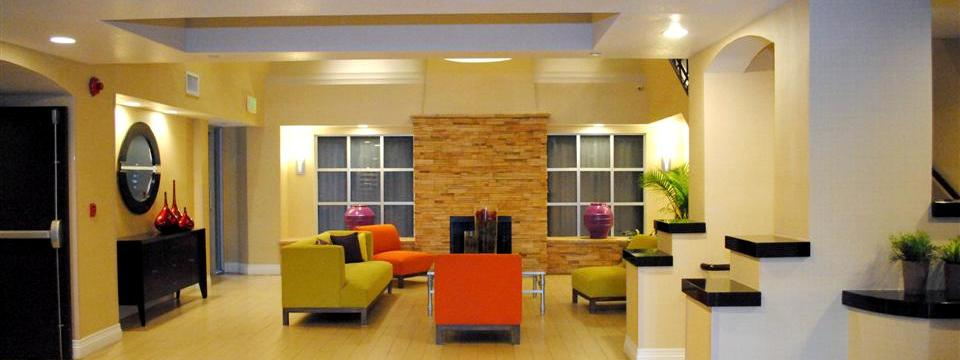 Spacious lobby with yellow couches, orange chairs and a fireplace