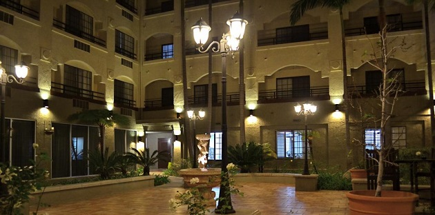 Hotel courtyard featuring a fountain and greenery