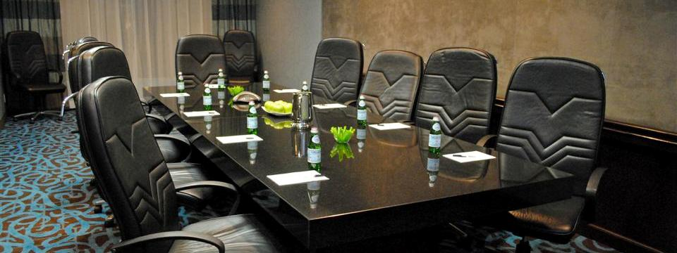 Boardroom with long table, leather chairs and waters