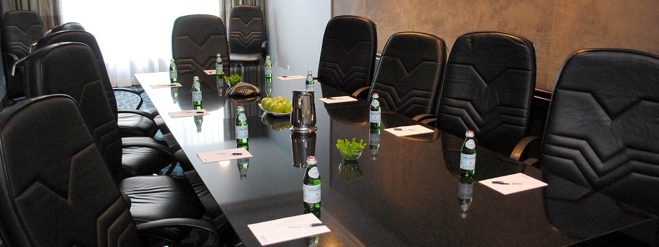 Boardroom with long table, leather chairs and water