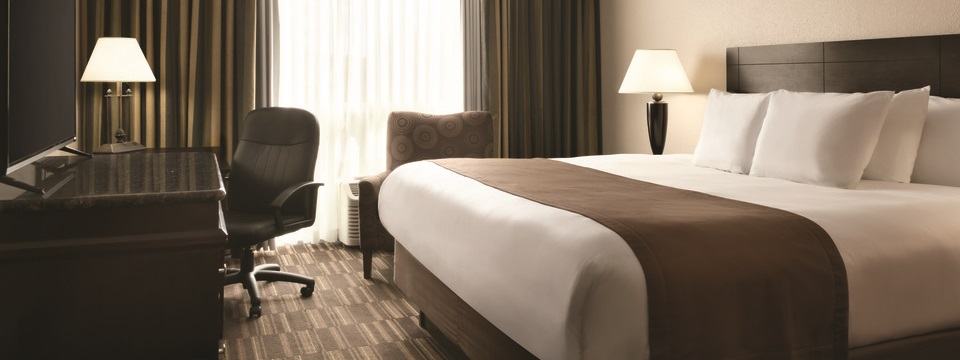 Hotel room featuring a king bed with a brown bedspread, a brown, patterned arm chair and a flat-screen TV