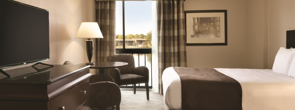 Hotel room with a queen bed, a flat-screen TV, two brown, patterned chairs and a view of the lake