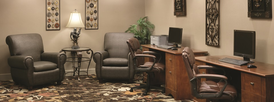Hotel business center with two gray armchairs, two brown leather office chairs and two desktop computers