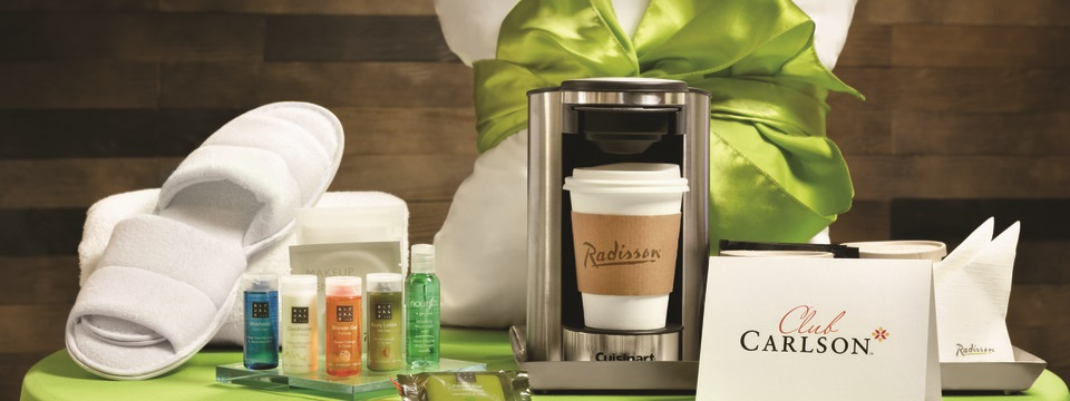 Hotel room amenities including slippers, a coffeemaker, and various lotions and shampoos