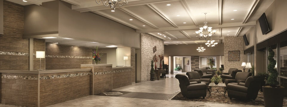 Hotel front desk and lobby area with armchairs, glass tables and mounted flat-screen TVs