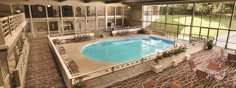 Indoor pool set against floor-to-ceiling windows and surrounded by patio chairs