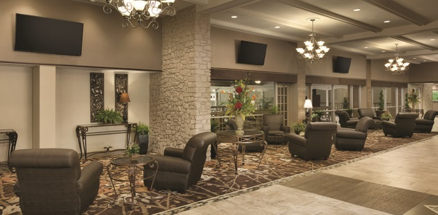 Hotel lobby with plush arm chairs, three mounted flat-screen TVs and a stone support column