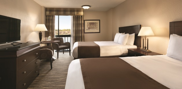 Hotel room with two queen beds, a flat-screen TV and checkerboard curtains featuring soothing earth tones