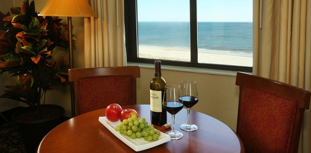 Hotel room with fresh fruit tray, wine glasses and ocean view