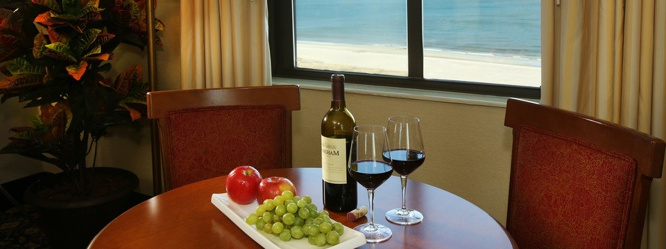Wine and fruit on table in hotel room overlooking the ocean