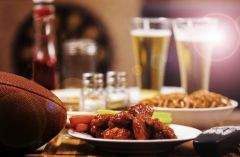 Table set with wings, pretzels, beer a football and a TV remote
