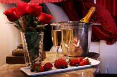 Roses, strawberries and champagne on bedside table