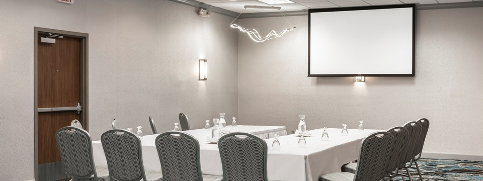 Well-lit meeting room in U-shape setup with projection screen