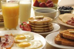 Breakfast spread with eggs, bacon, pancakes, fresh fruit and beverages