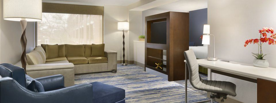 Hotel suite with couch, chaise lounge, desk and entertainment center