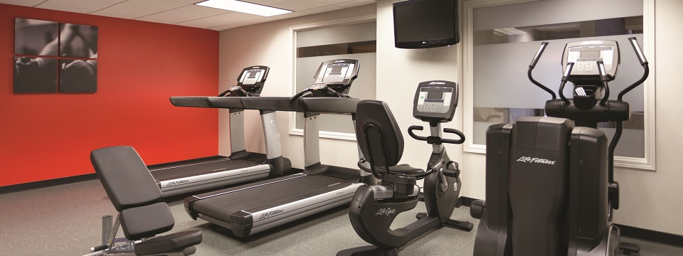 Hotel fitness center with exercise machines and a TV