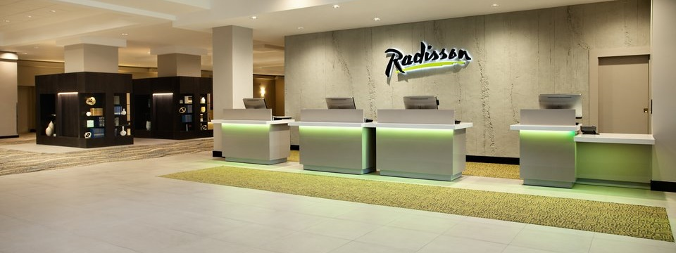 Spacious lobby with reception desk and green accents