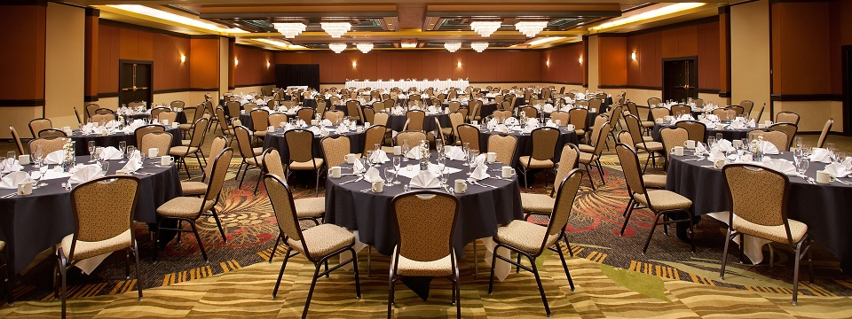 Ballroom featuring round tables and place settings