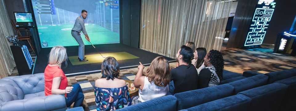 Man teeing up for virtual golf as friends watch from a sofa