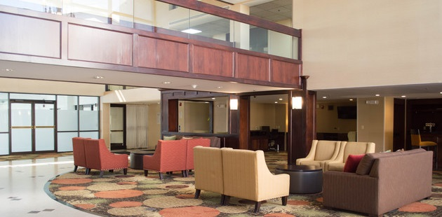 Modern hotel lobby with patterned accent carpet and plush armchairs