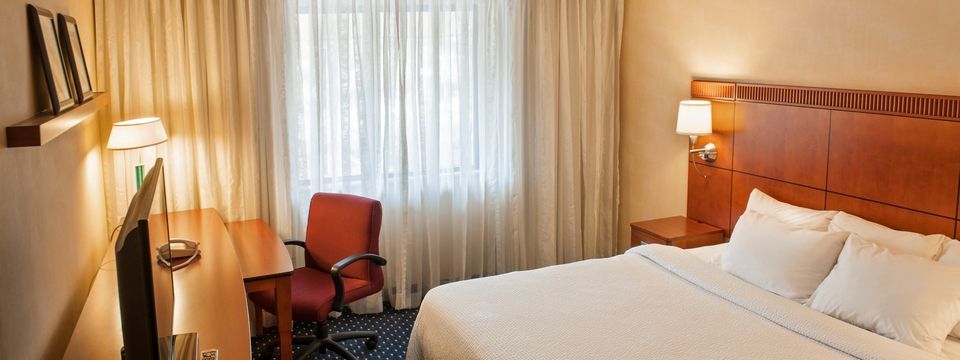 Hotel room with a king bed, desk and comfortable work chair