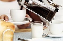 Woman receiving freshly poured coffee with breakfast