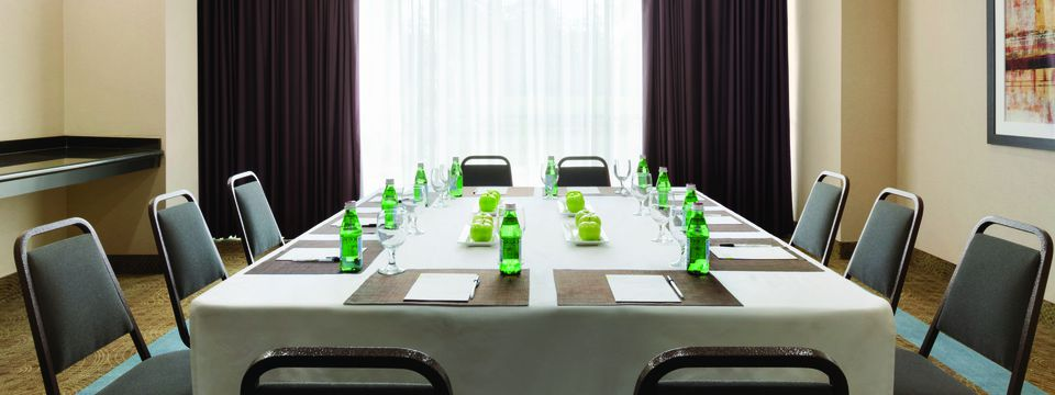Conference room featuring a table set with water, apples and writing supplies