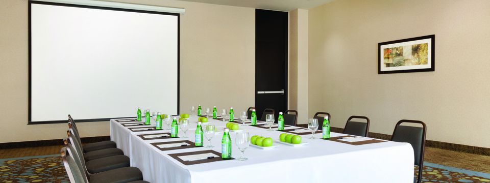 Meeting room with a conference table and projector screen