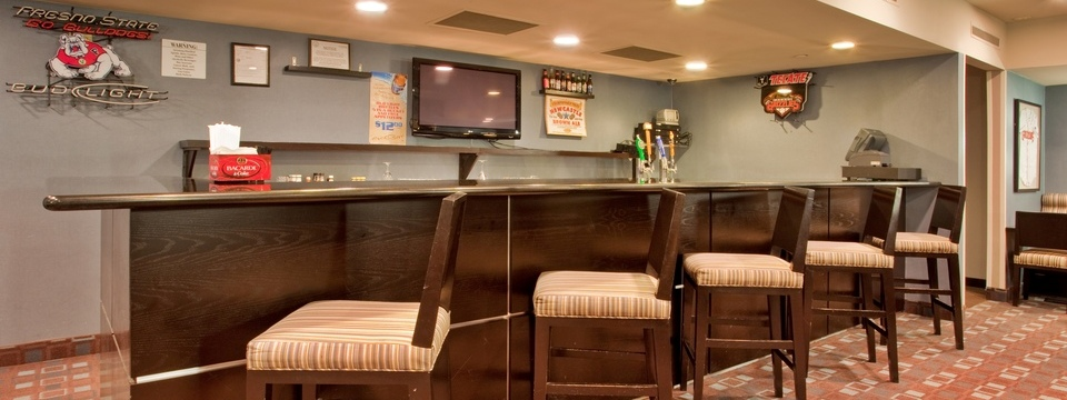Hotel bar with bar stools, beverages and flat-screen TV