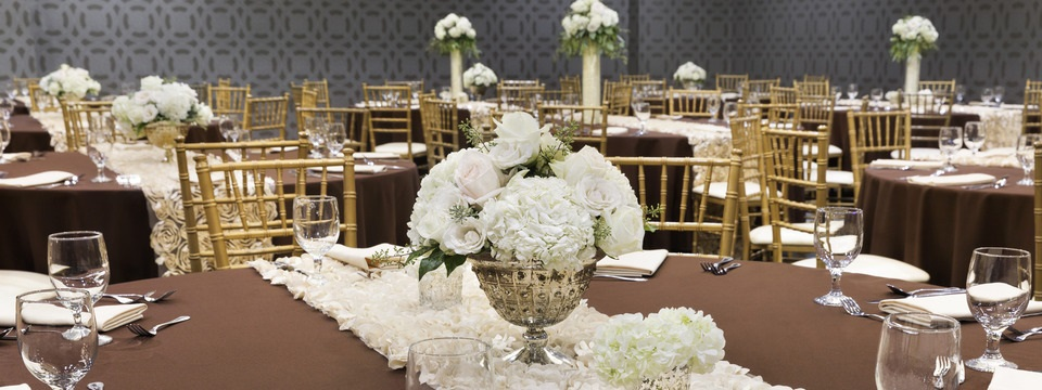 Formal table setting with glassware and elegant white floral arrangement