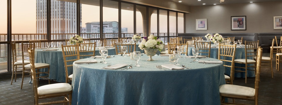 Formal event space with teal linens, table bouquets and city views