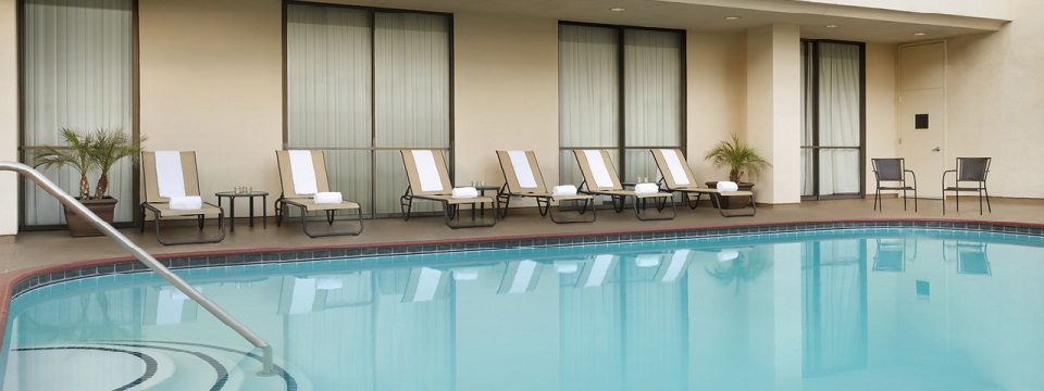 Outdoor pool surrounded by lounge chairs with towels