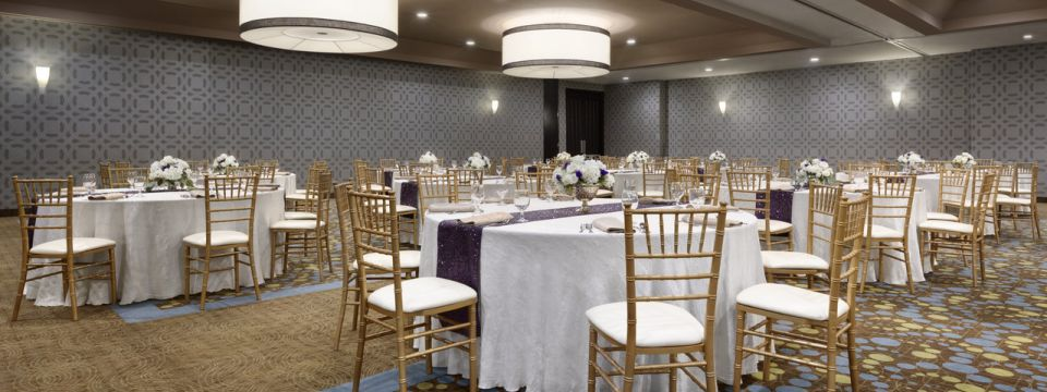 Elegant event space with round tables, purple accents and floral arrangements