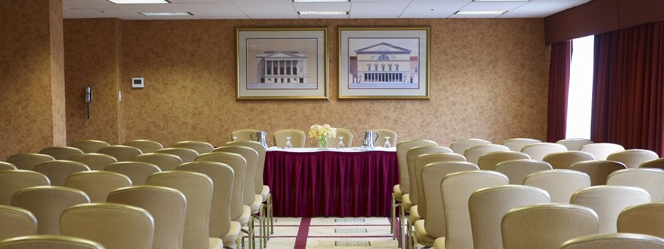 Rows of chairs face head table with maroon skirting