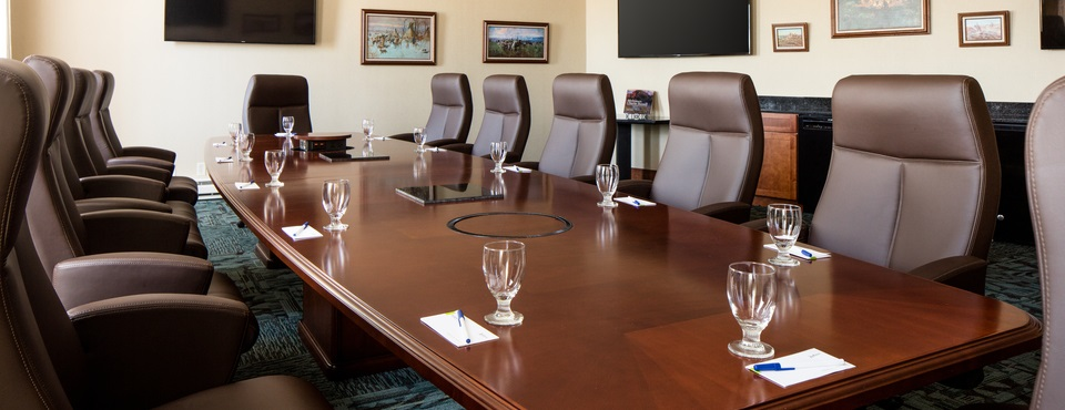 Meeting room with long table surrounded by chairs