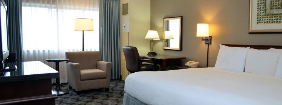 Hotel room with a king bed, desk and comfortable chair