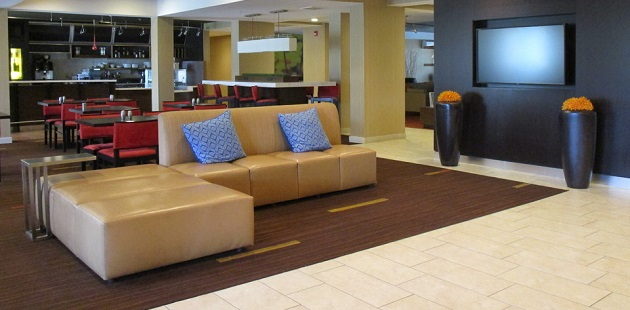 Hotel lobby with a tan sectional and a dining area