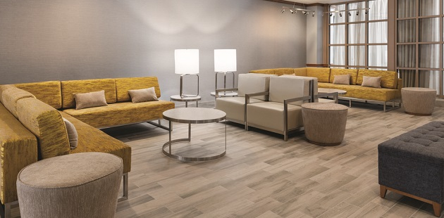 Welcoming hotel lobby with yellow sectionals and tan armchairs