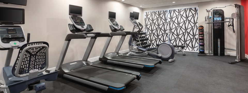 On-site fitness center with two treadmills, an elliptical, a multi-gym and a rack of medicine balls