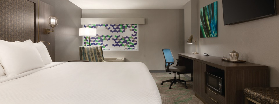 Hotel room featuring a king bed, a microwave and a window shade with geometric patterns