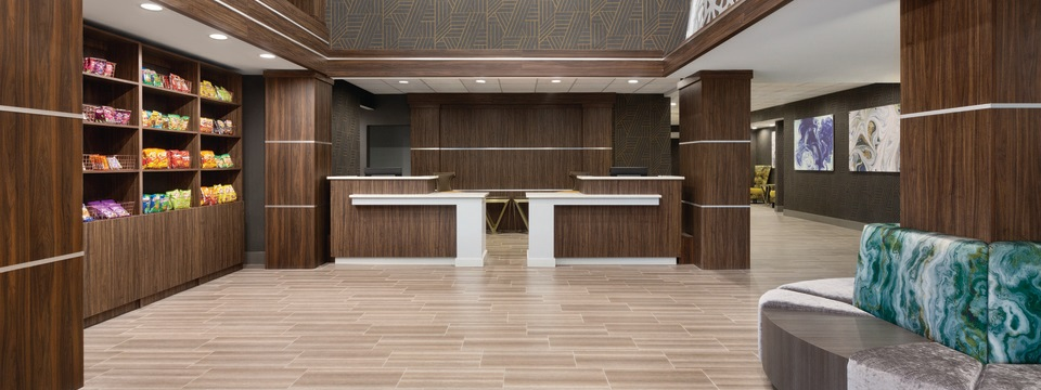 Reception area with comfortable seating, an on-site market and a front desk with wooden accents