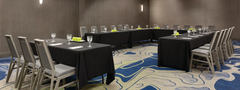 Meeting room with tables and chairs arranged in a U shape