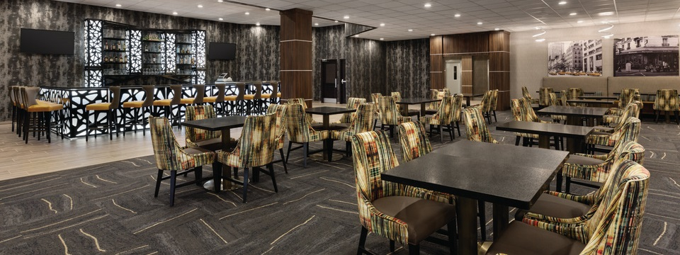 On-site restaurant with tables, patterned chairs and a fully stocked bar
