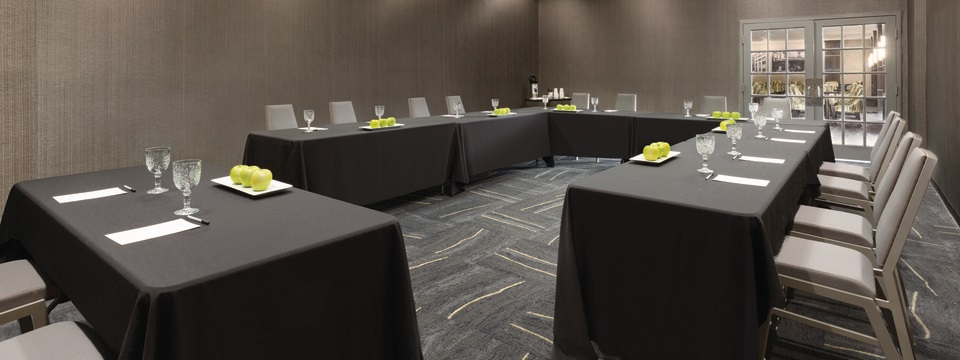 Meeting room tables set with apples, stationery and water glasses