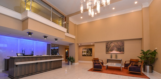 High-ceilinged lobby featuring a front desk and a comfortable seating area