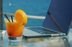 Cocktail and a laptop resting on a glass table