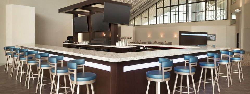 Hotel lobby bar with metallic blue bar stools and flat-screen TVs